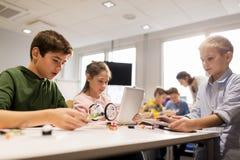 Niños con la PC de la tableta que programa en la escuela de la robótica Foto de archivo libre de regalías