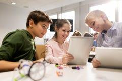 Niños con la PC de la tableta que programa en la escuela de la robótica Imagen de archivo libre de regalías
