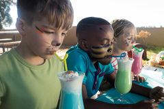 Niños con la pintura de la cara que tiene bebidas Imagenes de archivo