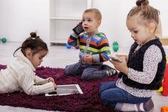 Niños con la tableta y los teléfonos fotografía de archivo libre de regalías
