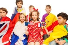 Niños con las banderas envueltas en diversas banderas Imagen de archivo libre de regalías