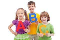 Niños con las cartas del ABC Foto de archivo