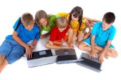 Niños con las computadoras portátiles Foto de archivo libre de regalías