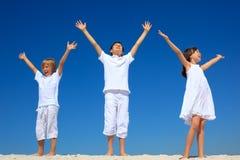 Niños con las manos levantadas Fotografía de archivo