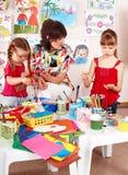 Niños con las pinturas del drenaje del profesor en sala de juegos. Fotografía de archivo