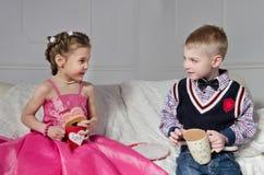 Niños con las tortas y las tazas Imagenes de archivo
