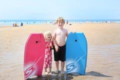 2 niños con los bodyboards que practican surf en woolacombe varan, Devon, u Imagenes de archivo