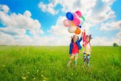 Niños con los globos que caminan en campo de la primavera Foto de archivo libre de regalías