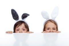 Niños con los oídos del conejito que miran a escondidas debajo de la tabla Fotos de archivo