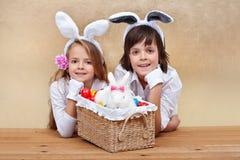 Niños con los oídos del conejito y la cesta de pascua Fotos de archivo