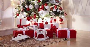 Niños con los regalos de Navidad debajo del árbol de navidad almacen de video