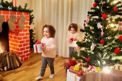 Niños con los regalos en la Navidad, nuevo Year& x27; s en el cuarto con th foto de archivo libre de regalías