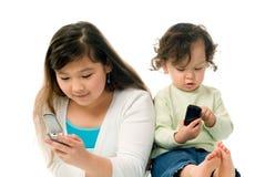 Niños con los teléfonos móviles. Imagenes de archivo