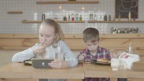 Niños con los teléfonos que disfrutan de la comida de alimentos de preparación rápida en café metrajes