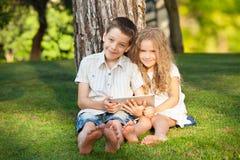 Niños con PC de la tableta al aire libre Foto de archivo libre de regalías