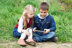 Niños con PC de la tableta al aire libre Imagen de archivo