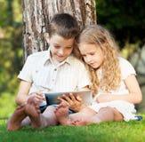 Niños con PC de la tableta al aire libre Imagenes de archivo