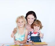 Niños con su madre con los pulgares para arriba Fotografía de archivo