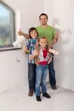 Niños con su padre que se prepara para pintar el cuarto imágenes de archivo libres de regalías