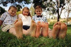 Niños con su toether de los pies en la hierba Fotos de archivo libres de regalías