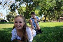 Niños con sus pies en el aire que es cosquilleado imagenes de archivo