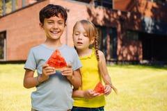 Niños contentos que comen una sandía madura Fotos de archivo