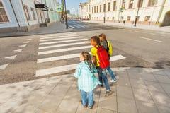 Niños cuidadosos que cruzan la calle Imágenes de archivo libres de regalías