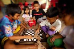 Niños de áreas pobres en ajedrez del juego Imagenes de archivo