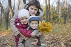 Niños de abarcamiento de la madre en parque Imagenes de archivo