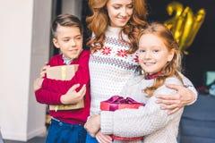 Niños de abarcamiento de la madre con los regalos de la Navidad Imagen de archivo libre de regalías