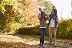 Niños de Autumn Walk With Parents Carrying en hombros imagen de archivo libre de regalías