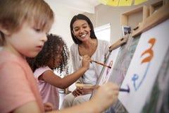 Niños de ayuda de At Montessori School del profesor en Art Class Fotos de archivo libres de regalías