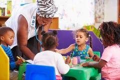 Niños de ayuda del profesor en una clase preescolar fotos de archivo libres de regalías