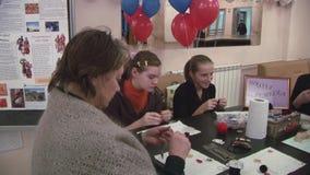 Niños de enseñanza de la mujer cómo hacer los colgantes hechos a mano en la tabla manía creación holiday metrajes