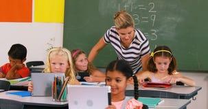 Niños de enseñanza del profesor en la tableta digital metrajes