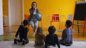 Niños de enseñanza del profesor preescolar sobre el globo almacen de video