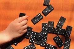 Niños de enseñanza para jugar al juego de los dominós en un fondo de madera imágenes de archivo libres de regalías