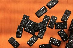 Niños de enseñanza para jugar al juego de los dominós en un fondo de madera foto de archivo