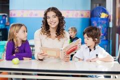 Niños de Holding Book With del profesor en el escritorio Imagen de archivo