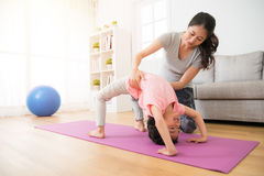 Niños de la ayuda del profesor que hacen la acción de la yoga Imagen de archivo libre de regalías