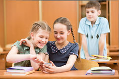 Niños de la escuela con los teléfonos celulares en sala de clase Imagen de archivo libre de regalías