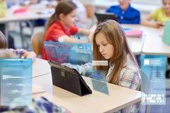 Niños de la escuela con PC de la tableta en sala de clase foto de archivo