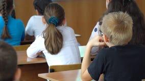 Niños de la escuela en la sala de clase que se sienta en sus escritorios almacen de metraje de vídeo