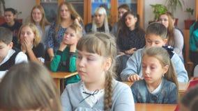 Niños de la escuela en la sala de clase que se sienta en sus escritorios y escuchar el profesor metrajes