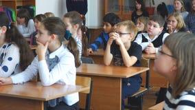 Niños de la escuela en la sala de clase que se sienta en sus escritorios y escuchar el profesor almacen de video