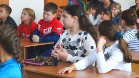 Niños de la escuela en la sala de clase que se sienta en sus escritorios y escuchar el profesor almacen de metraje de vídeo