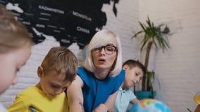 Niños de la escuela primaria o de la guardería que dibujan en la sala de clase con la ayuda del profesor Retrato de un caucásico  almacen de video