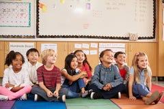 Niños de la escuela primaria que se sientan en piso de la sala de clase Imagenes de archivo