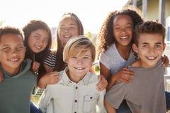 Niños de la escuela primaria que sonríen a la cámara durante rotura de la escuela fotos de archivo libres de regalías