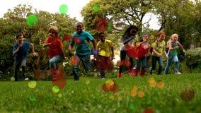 Niños de la escuela que corren en la cámara lenta hacia la cámara en un parque